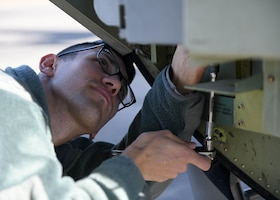 An Airman uses a tool to unscrew a bolt on a C-130J Super Hercules.