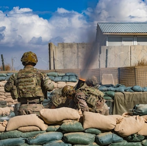 Soldiers fire mortar.