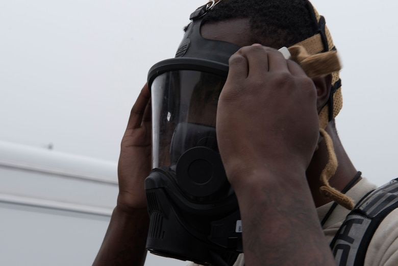 Airman 1st Class Cameron Butler, 4th Civil Engineer Squadron emergency management hazardous material team technician, dons a gasmask during a Hazardous Material Spill Response exercise, Dec. 9, 2019, in Goldsboro, N.C.