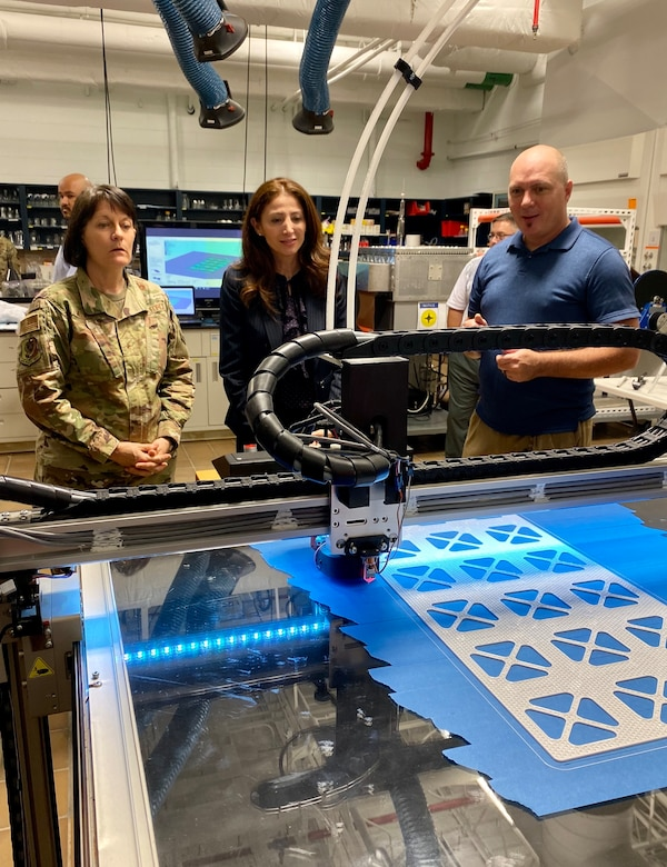 From left to right, Brigadier Gen. Patrice Melancon, Tyndall Program Management Office executive director, Dr. Julia Nesheiwat, Florida Chief Resilience Officer and Dr. Jeff Owens, Air Force Civil Engineer research scientist, observe a 3D printer producing materials for testing during a visit to the AFCEC research lab.