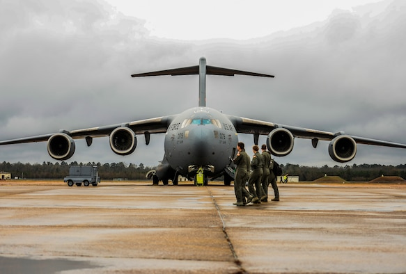 Four Airmen walk in front of a C-17 Globemaster III Dec. 10, 2019, at Columbus Air Force Base, Miss. The C-17 measures 174 feet long (53 meters) with a wingspan of 169 feet, 10 inches (51.75 meters). (U.S. Air Force photo by Airman Davis Donaldson)