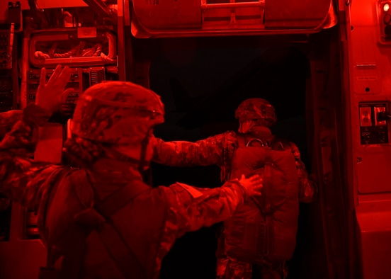 Capt. Monica Notzon, CO Commander, assigned to the 118th MP CO (ABN), from Fort Bragg, N.C., communicates with a jumpmaster and loadmaster over the Nevada Testing and Training Range, Nevada., December 7, 2019.