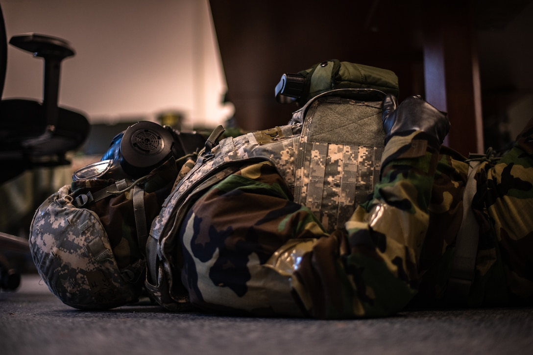 A U.S. Air Force Airman dressed in Mission-Oriented Protective Posture gear takes cover under a desk during exercise Operation Varsity 19-04 at Ramstein Air Base, Germany, Dec. 10, 2019. Airmen had to seek shelter while a simulated air strike occurred over the installation. (U.S. Air Force photo by Staff Sgt. Devin Boyer)