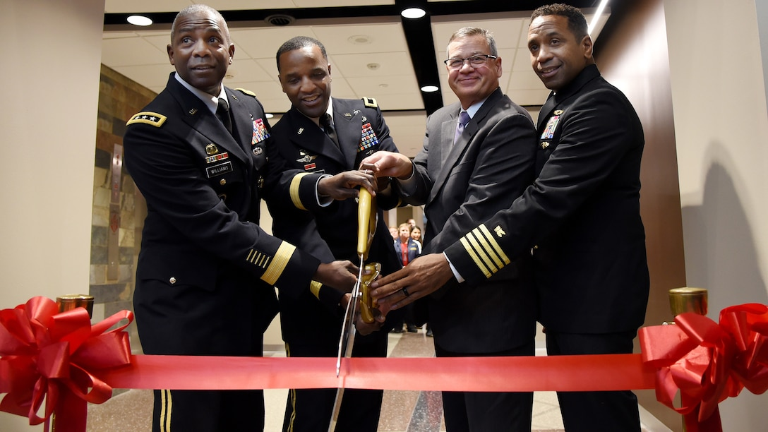 Four senior leaders use over-sized scissors to cut a ribbon