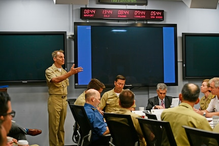 A Navy admiral talks to a group of military personnel.