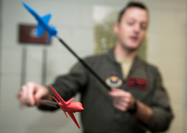 "An Euro-NATO Joint Jet Pilot Training Program student pilot uses red and blue planes to show aircraft formation types at Sheppard Air Force Base, Texas, Dec. 10, 2019. The red plane represents the ""bandit plane"" which basically means the ""bad"" plane, while the blue plane represents the ENJJPT pilot. Using the red and blue planes, the instructor can show different scenarios and where the ENJJPT pilots should be in each situation. (U.S. Air Force photo by Senior Airman Pedro Tenorio)"