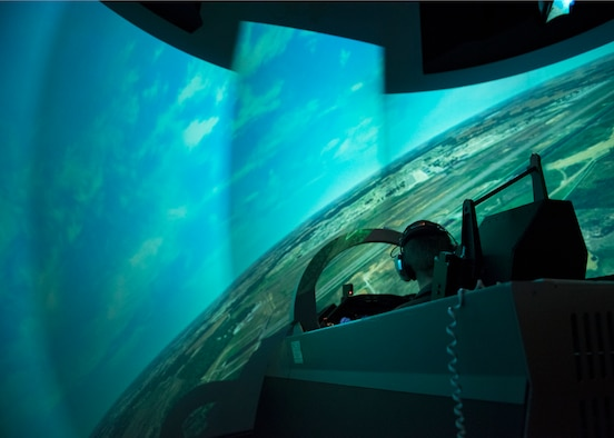 A Euro-NATO Joint Jet Pilot Training Program student pilot, simulates flying a T-6 Texan II in a Operational Flight Training simulator at Sheppard Air Force Base, Texas, Dec. 10, 2019. The OFT can be used for multiple simulations as it has both the flight-deck simulator and a 360 field of view. It is also made in a way that tricks the users brain to make them feel as if they are actually turning, going up, etc.. (U.S. Air Force photo by Senior Airman Pedro Tenorio)