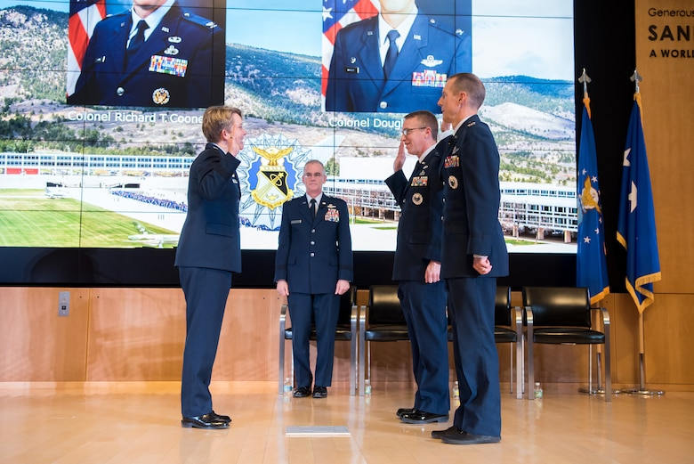 The dean of faculty, Brig. Gen. Linell Letendre, swears in the new permanent professors alongside the Academy superintendent, Lt. Gen. Jay Silveria, during an investiture ceremony in Polaris Hall at the U.S. Air Force Academy, Colo., Dec. 6, 2019. The new professors invested include Col. Richard Cooney, department of behavioral sciences and leadership, and Col. Douglas Wickert, department of aeronautics. (U.S. Air Force photo by Trevor Cokley)