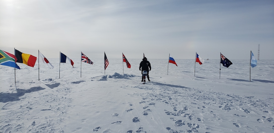 Master Sgt. Justin Rogers, the 108th Wing Safety Office occupational and safety health specialist, stands behind the South Pole in Antarctica, Nov. 26, 2019. Rogers participated in Operation DEEP FREEZE (ODF), a joint service on-going Defense Support to Civilian Authorities (DSCA) activity in support of the National Science Foundation (NSF), lead agency for the United States Antarctic Program.