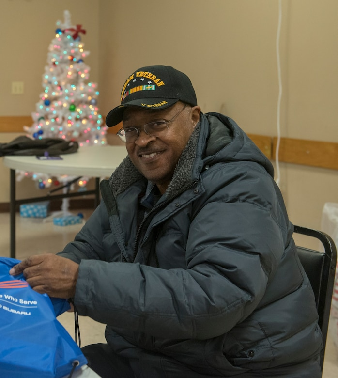 Clinton Jones, Offutt Advisory Council, fills holiday cheer bags Dec. 10, 2019. Members of the Bellevue Chamber of Commerce and Offutt Air Force Base leadership filled holiday cheer bags for dorm residents here.