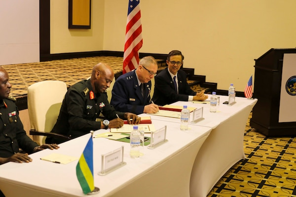 Rwanda's Chief of Defence Staff, Gen. Jean-Bosco Kazura, and U.S. Air Force Maj. Gen. Daryl Bohac, Nebraska National Guard adjutant general, sign a document officially forming a new partnership under the State Partnership Program, Dec. 12, 2019, in Kigali, Rwanda. Watching the signing is Peter Vrooman, U.S. ambassador to Rwanda.