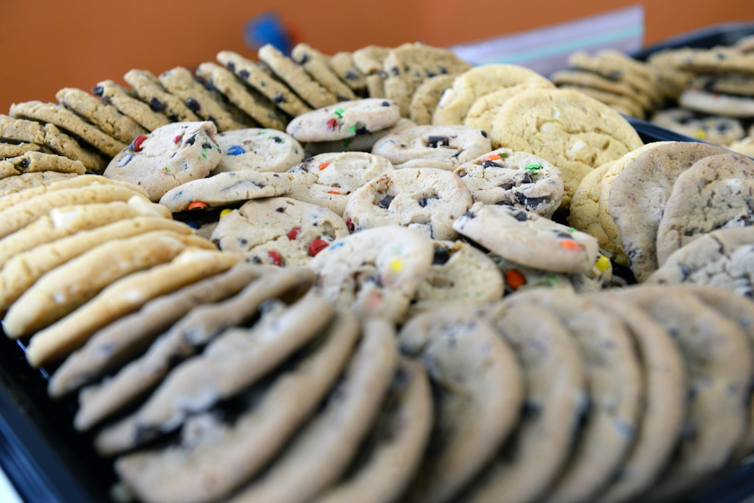 The Ellsworth Spouse's Club arranges homemade and store-bought cookies for the Cookie Drive at Ellsworth Air Force Base, S.D., Dec. 9, 2019. The Club received roughly $277 in monetary donations and packaged more than 12,000 cookies, spreading holiday cheer to more than 700 dormitory single Airmen. (U.S. Air Force photo by Airman Quentin K. Marx)