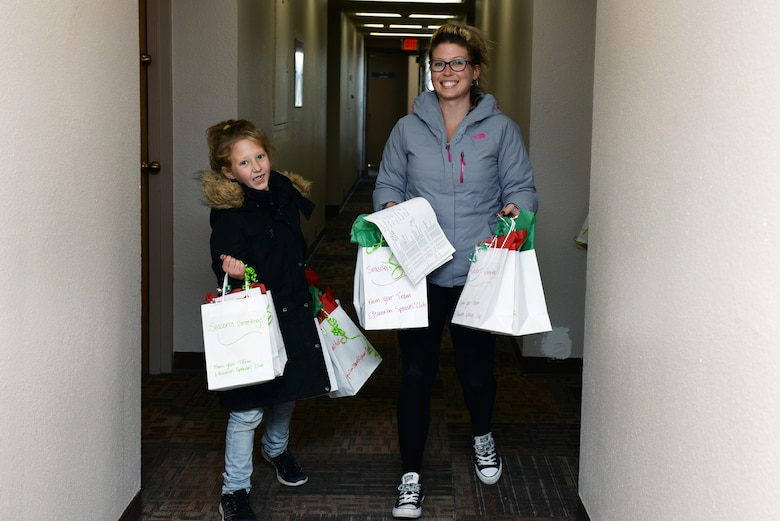 Heather Ryan, the Ellsworth Spouse's Club Fundraising chairperson, and a student from the St. Paul's School deliver cookies to Airmen residing in the dormitories at Ellsworth Air Force Base, S.D., Dec. 9, 2019. More than 12,000 cookies were packaged and delivered to more than 700 dorm Airmen, spreading holiday cheer to those away from their families this year. (U.S. Air Force photo by Airman Quentin K. Marx)