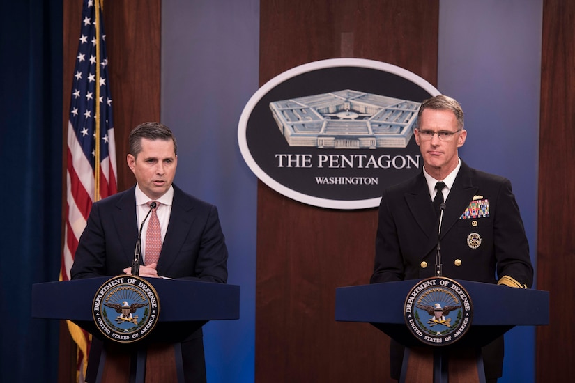 Two men, one wearing a military uniform, stand behind podiums and speak to reporters.