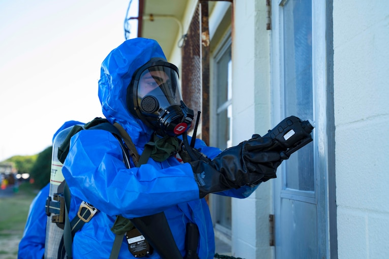 A Marine wears a bio hazard suit while checking a door.