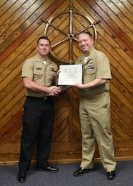 U.S. Navy Petty Officer 2nd Class Adam Stidsen, 316th Training Squadron cryptologic technician, receives a Letter of Commendation for being the Top Graduate of the Navy Analysis and Reporting course from Master Chief Petty Officer Joseph Rynolds, Navy senior enlisted leader, at the Center for Information Warfare Training Detachment on Goodfellow Air Force Base, Texas, Dec. 12, 2019. Stidsen completed the 560 hour course with the academic average of 98.5%. (U.S. Air Force photo by Airman 1st Class Abbey Rieves)