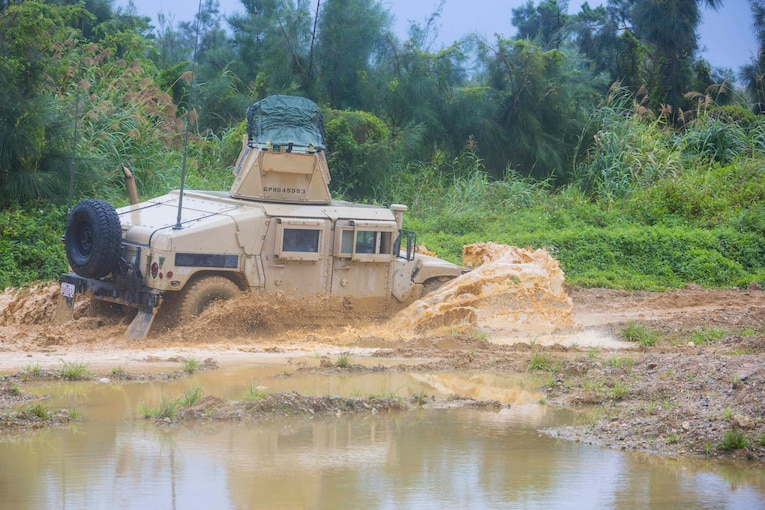 A military vehicle drives through mud and water.