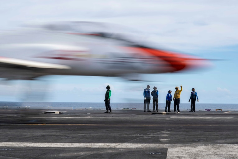 Sailors stand on a ship watch a plane land.