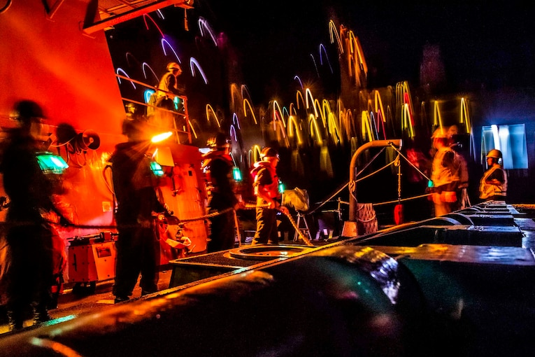 Sailors stand on a ship with red lights surrounding.