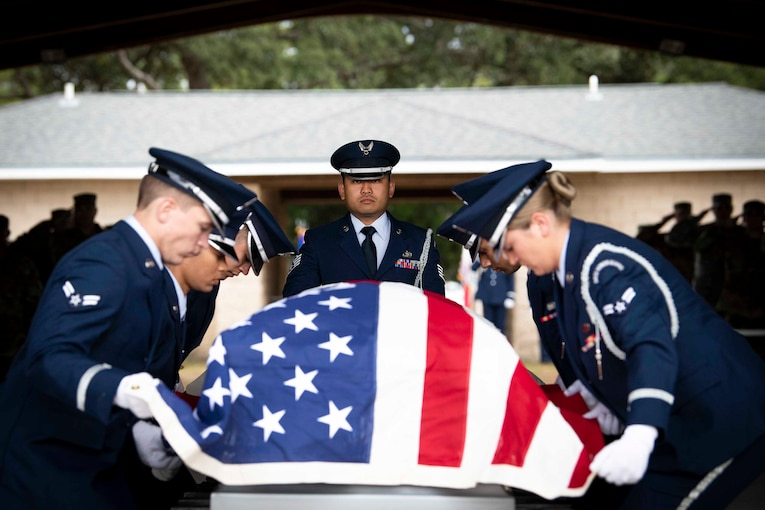 Airmen hold an American flag over a casket.