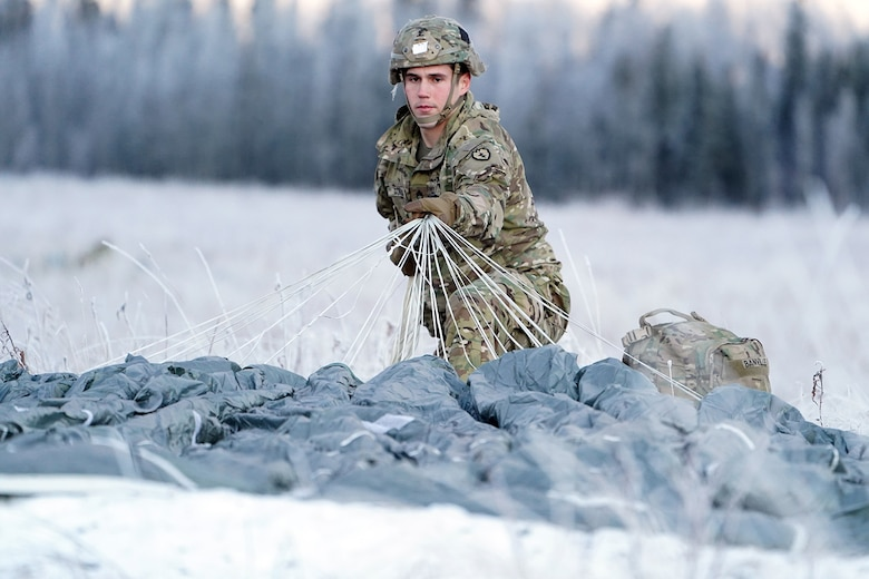 Army Staff Sgt. Joshua Couillou, a native Buford, Ga., assigned to the 1st Battalion, 501st Parachute Infantry Regiment, 4th Infantry Brigade Combat Team (Airborne), 25th Infantry Division, U.S. Army Alaska, gathers up his parachute after a jump on Malemute drop zone at Joint Base Elmendorf-Richardson, Alaska, Dec. 11, 2019. The Soldiers are part of the Army's only Pacific airborne brigade with the ability to rapidly deploy worldwide, and are trained to conduct military operations in austere conditions.