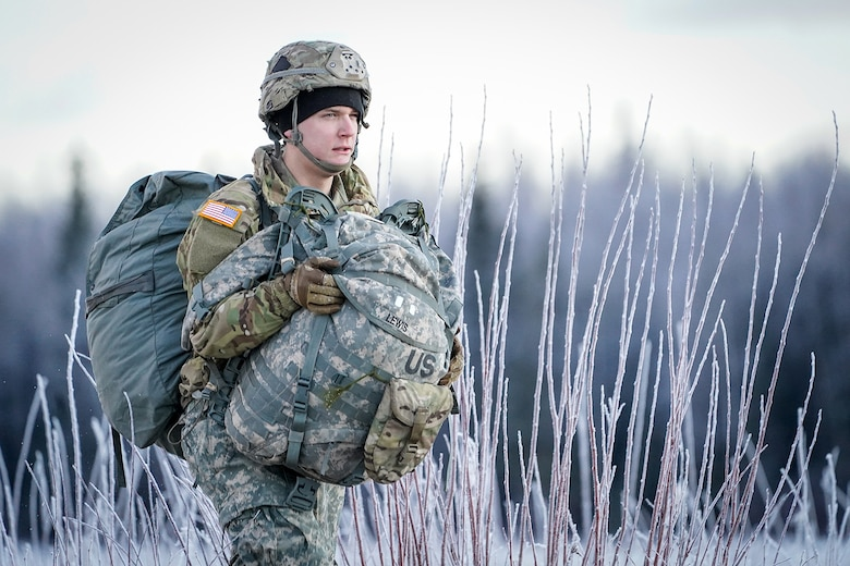 Army Pfc. Rhett Lewis, assigned to the 1st Battalion, 501st Parachute Infantry Regiment, 4th Infantry Brigade Combat Team (Airborne), 25th Infantry Division, U.S. Army Alaska, makes his way to a rally point after conducting a parachute jump on Malemute drop zone at Joint Base Elmendorf-Richardson, Alaska, Dec. 11, 2019. The Soldiers are part of the Army's only Pacific airborne brigade with the ability to rapidly deploy worldwide, and are trained to conduct military operations in austere conditions.
