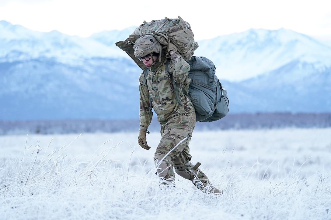 Army Pfc. Evan Samuel, assigned to the 2nd Battalion, 377th Parachute Field Artillery Regiment, 4th Infantry Brigade Combat Team (Airborne), 25th Infantry Division, U.S. Army Alaska, makes his way to a rally point after conducting a parachute jump on Malemute drop zone at Joint Base Elmendorf-Richardson, Alaska, Dec. 11, 2019. The Soldiers are part of the Army's only Pacific airborne brigade with the ability to rapidly deploy worldwide, and are trained to conduct military operations in austere conditions.
