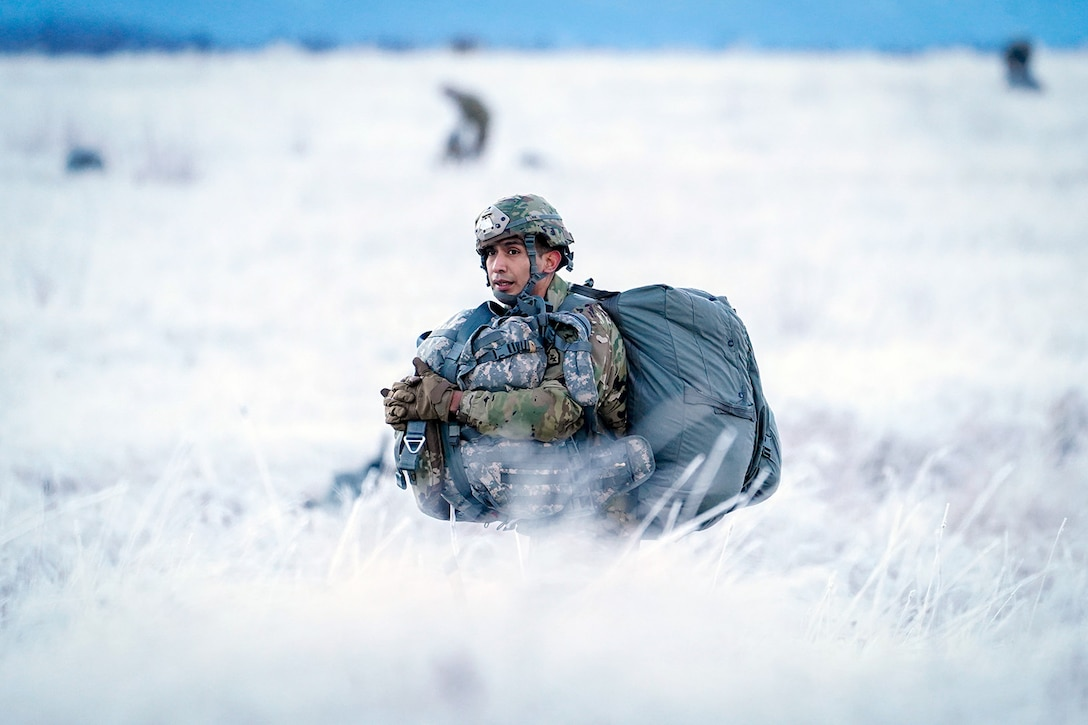 Army Pvt. Pedro Lara, assigned to the 6th Brigade Engineer Battalion (Airborne), 4th Infantry Brigade Combat Team (Airborne), 25th Infantry Division, U.S. Army Alaska, makes his way to a rally point after conducting a parachute jump on Malemute drop zone at Joint Base Elmendorf-Richardson, Alaska, Dec. 11, 2019. The Soldiers are part of the Army's only Pacific airborne brigade with the ability to rapidly deploy worldwide, and are trained to conduct military operations in austere conditions.