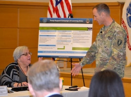 """Army Col. Kennon Gilliam, strategic wargaming director for the Army Center for Strategic Leadership, right, discusses the """"Game of 23"""" with DLA Troop Support Product Test Center Analytic lead scientist Jamie Hieber during an event Dec. 5, 2019, in Philadelphia."""