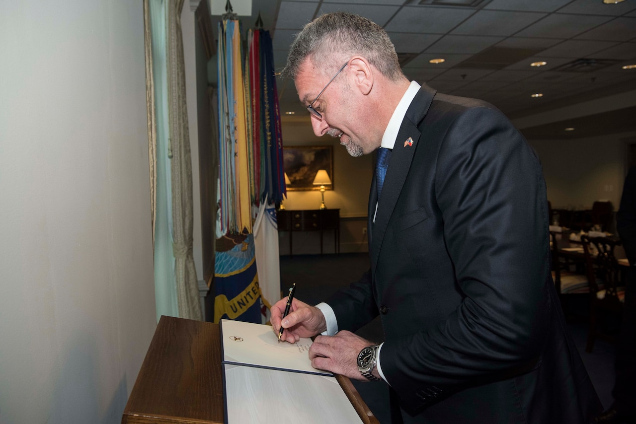 A man writes in a book on a podium.