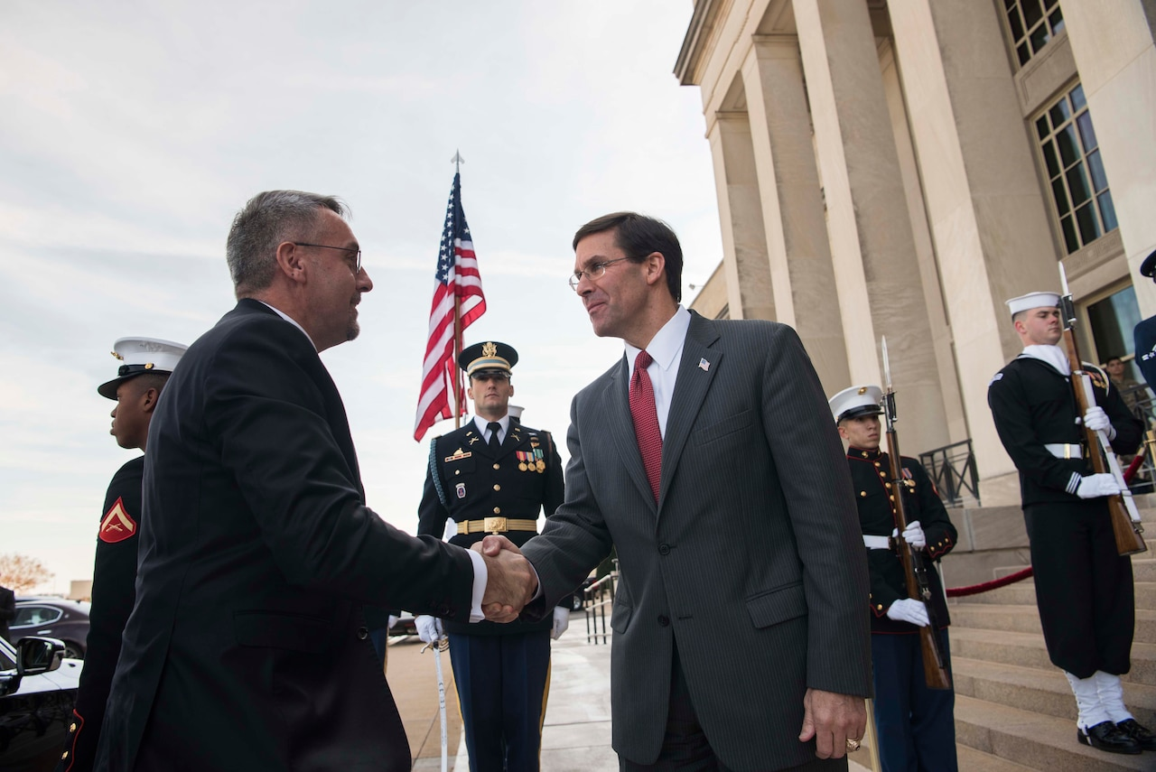 Two men shake hands. Military service members in dress uniforms stand in a row in the background.