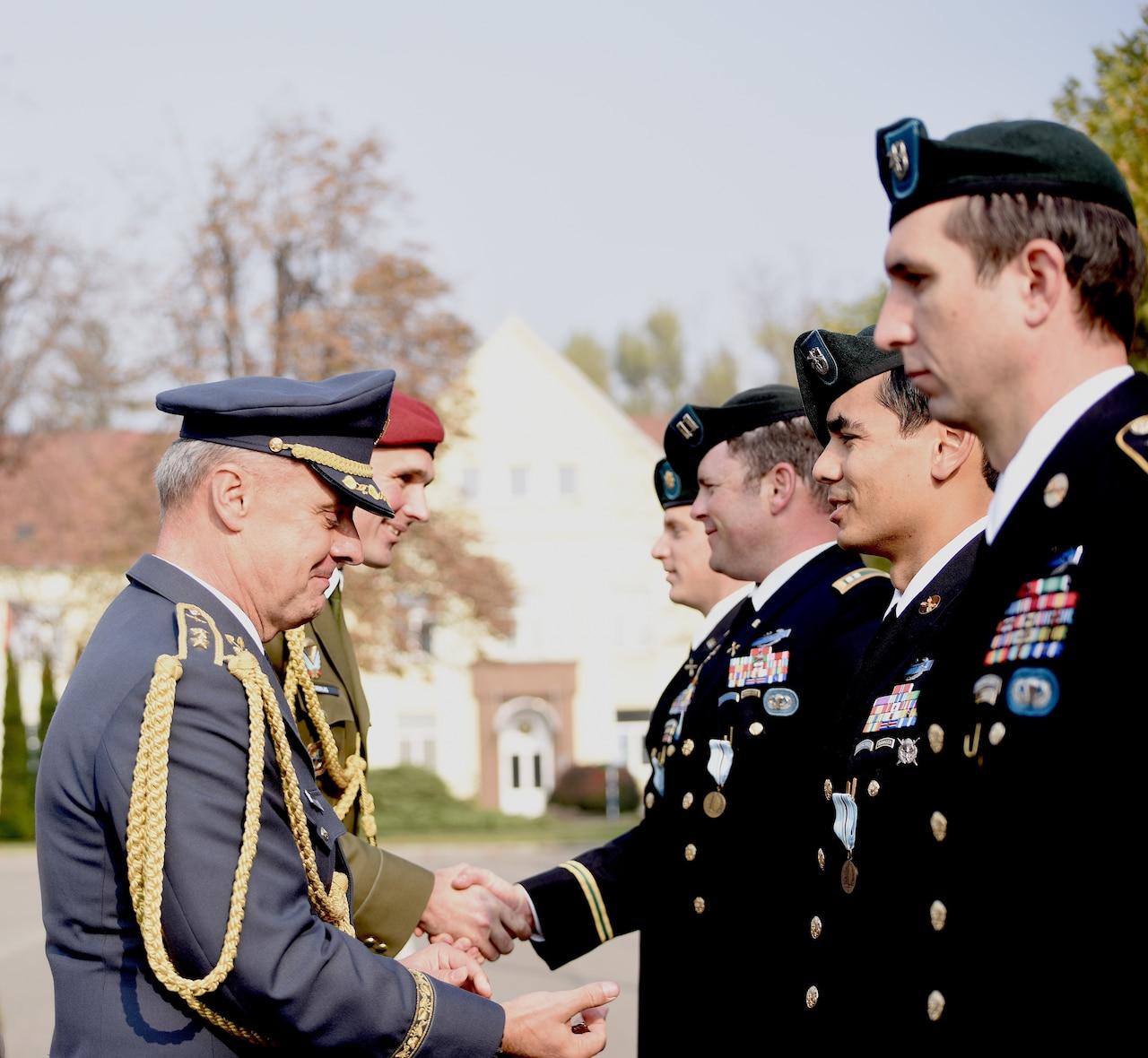 Men in military dress uniforms shake hands.