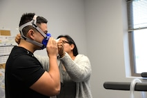 Photo of a human promotion coordinator adjust VO2 test mask on a client