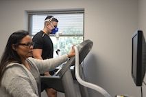 Photo of a health promotion coordinator monitoring vitals on a screen for a person walking on a treadmill