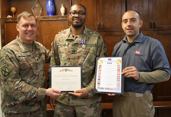 Lt. Col. Dan Hayden, Afghanistan District Deputy Commander presents the Global War on Terrorism Medal to Derland Ellison, who redeployed from the Afghanistan District, while Adam Walker, Deputy Construction Chief, Bagram Resident Office displays the NATO medal certificate Ellison was awarded.