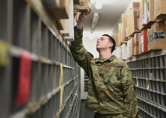 Senior Airman Tristan Greco, 51st Force Support Squadron postal clerk, searches for a customer's package at the post office on Osan Air Base, Republic of Korea, Dec. 11, 2019. The base post office receives one to two full mail trucks on an average day. (U.S. Air Force photo by Senior Airman Denise Jenson)