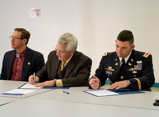 Fernando Macias (center), county manager, Dona Ana, and Lt. Col. Dale Caswell, commander, U.S. Army Corps of Engineers, Albuquerque District sign the Section 205 Small Flood Risk Management Cost Sharing Agreement during a signing ceremony at the Hatch Community Center, Hatch, New Mexico, Dec. 10, 2019. The purpose of signing the cost sharing agreement is to establish terms of funding, construction, and operation, maintenance, repair, replacement and rehabilitation of the project. USACE-Albuquerque District expects to begin the design phase of this project this coming spring.
