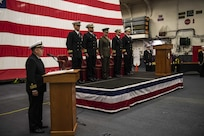 SASEBO, Japan (Dec. 11, 2019) Lt. Cmdr. Kenneth Zilka introduces the official party during the change of command ceremony for Amphibious Squadron (PHIBRON) 11 in the hangar bay of amphibious assault ship USS America (LHA 6). Capt. Richard Lebron relieved Capt. Jim McGovern as commodore of the only forward-deployed amphibious squadron in the U.S. Navy. America, part of Commander, PHIBRON 11 and Expeditionary Strike Group (ESG) 7, is operating in the Indo-Pacific region to enhance interoperability with partners and serve as a ready-response force for any type of contingency.
