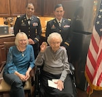 Freda Haworth Coate (front row, right) holds the Army Nurse Corps Association coin given to her by Lt. Col. Karen Santiago (back row, left) and Lt. Col. Teresa Shiels, both with the 228 Combat Support Hospital in San Antonio. The coin was given to Coate during her 100th birthday celebration Nov. 20 in Leander, Texas. Coate served in the U.S. Army Nurse Corps in World War II in the South Pacific from 1943-45.