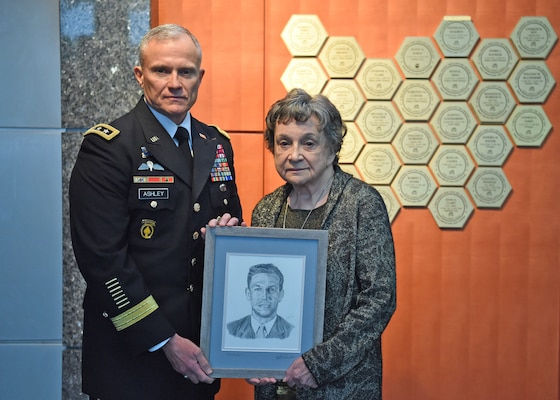 Defense Intelligence Agency Director Lt. Gen. Robert Ashley Jr., presents Dr. Blanka Shadrin a drawing of her husband, Nicholas Shadrin, after unveiling his plaque on the DIA Patriots Memorial. After defecting from the Soviet Union, Nicholas Shadrin worked at DIA while also serving as a double agent for the FBI. On a mission in Vienna in 1975, Shadrin was abducted by the KGB and killed from a sedative overdose.