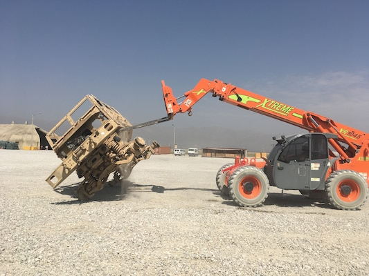 An equipment operator from the property management contractor performs the final steps of the ammo inspection process, a 90-degree roll-over of the vehicle.