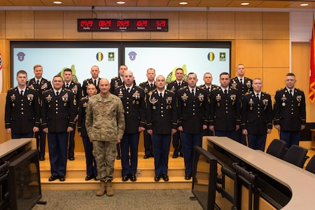 18 Army Soldiers standing on a stage after receiving their awards.