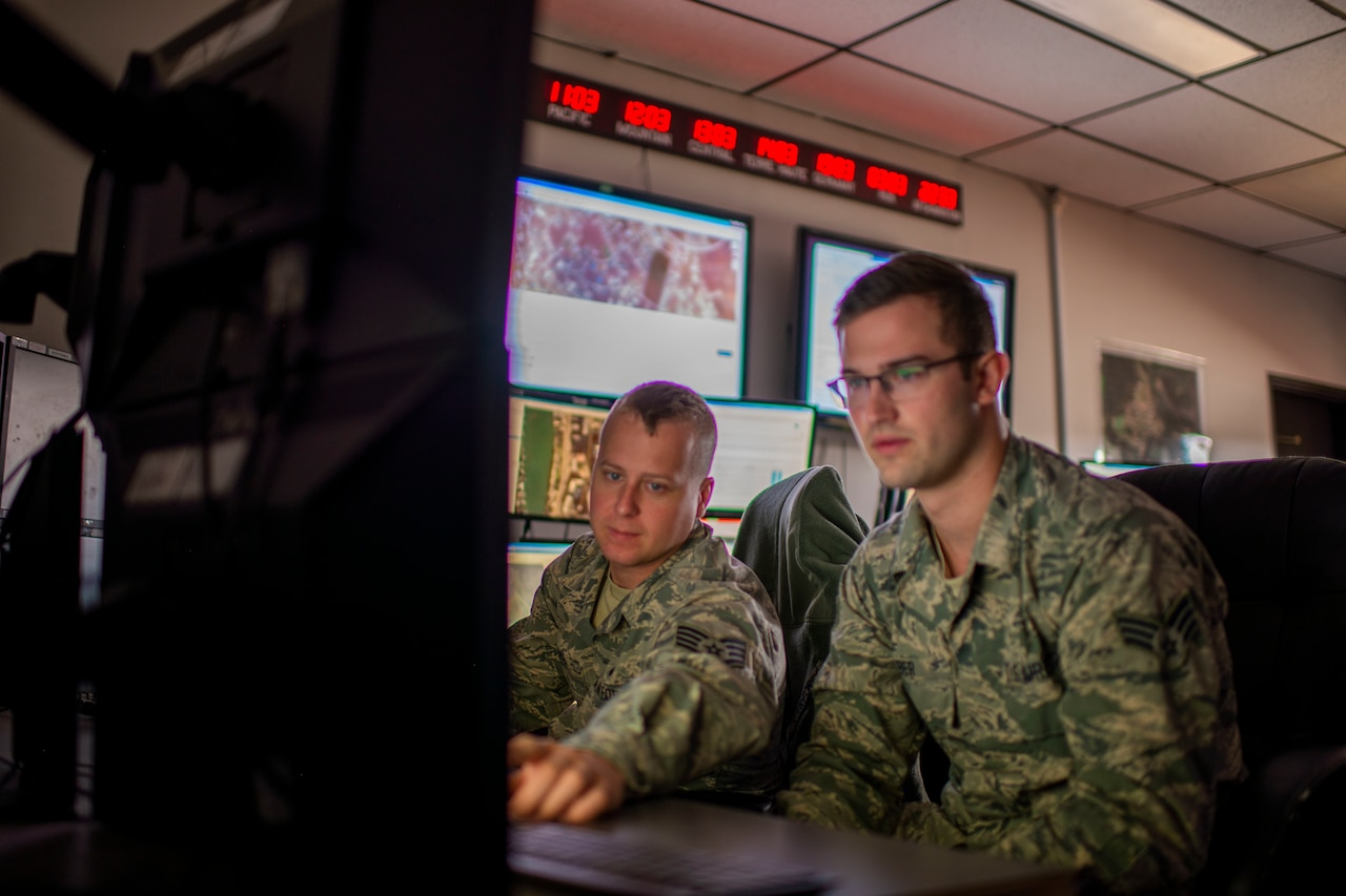 Two airmen focus on a computer screen.