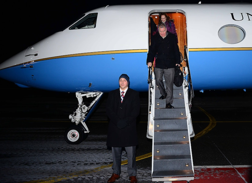 Two people walk down steps off a jet.