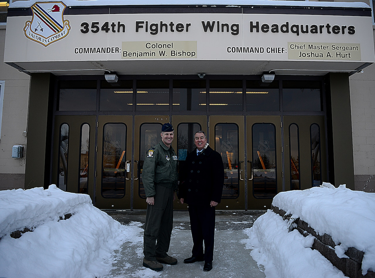 A civilian and an Air Force officer stand in front of a building with snow banks lining the entrance path.