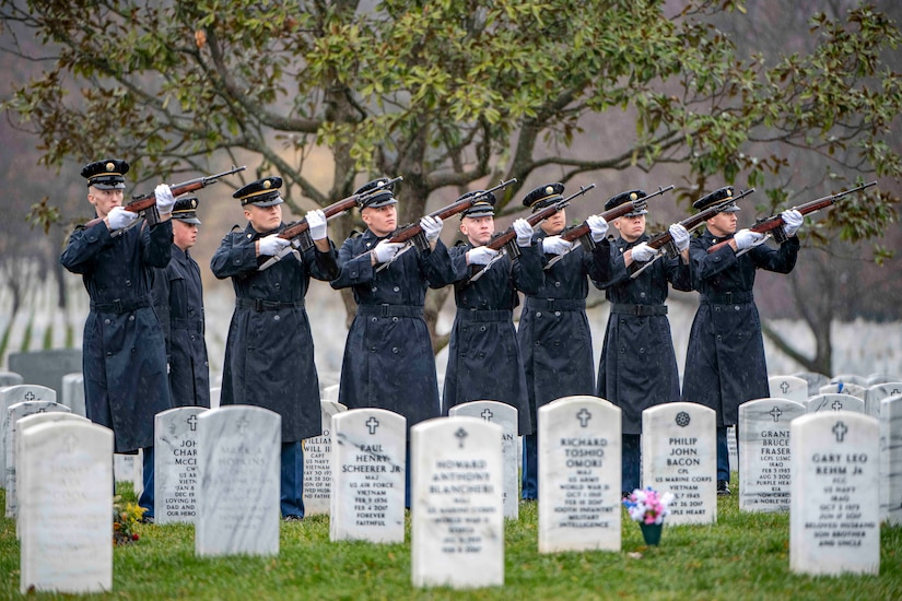 A group of soldiers stand in a line holding their rifles near tombstones.
