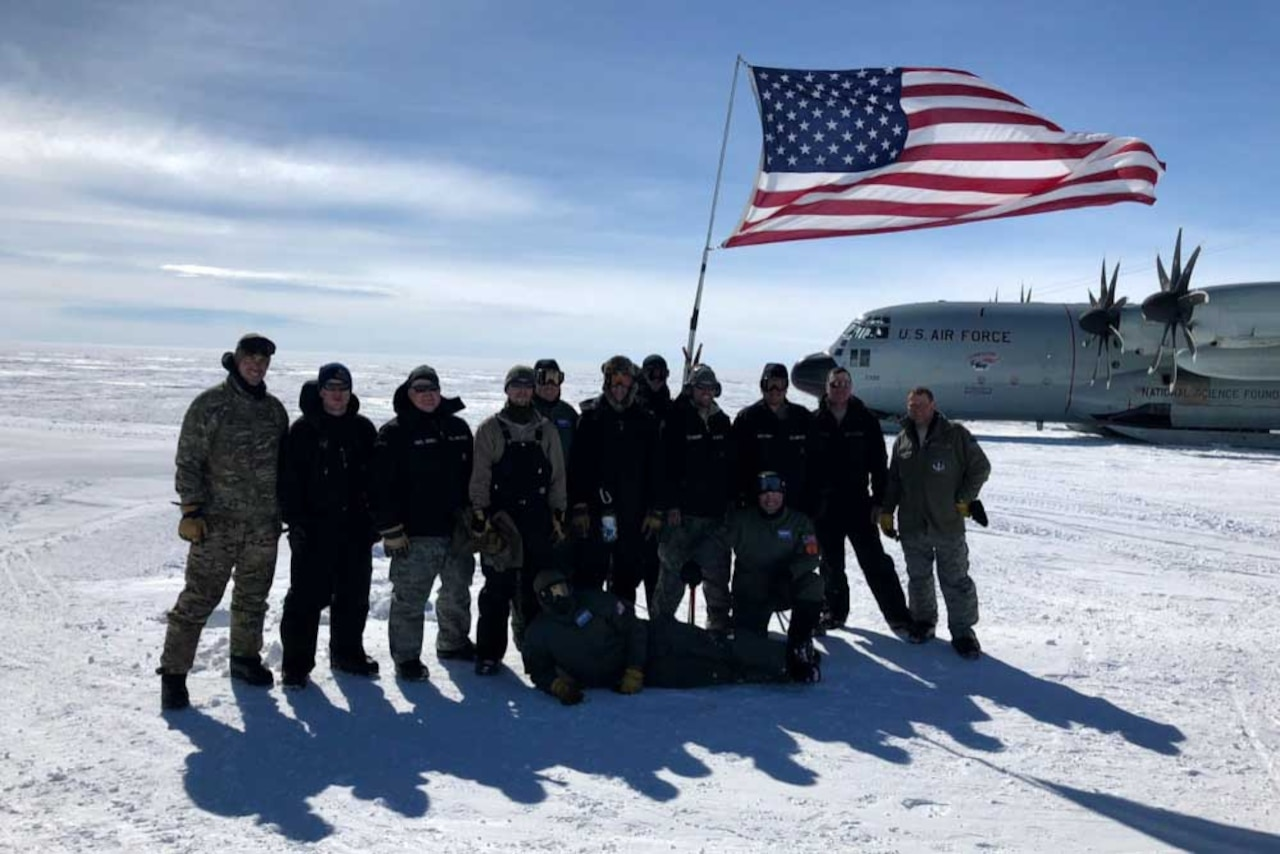 Airmen display an American flag in the Arctic.
