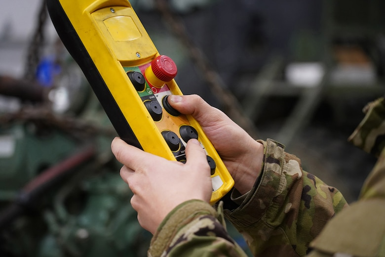 A soldier assigned to the 109th Transportation Company, 17th Combat Sustainment Support Battalion, U.S. Army Alaska, controls a hoist while moving a damaged engine from an M984A2 Heavy Expanded Mobility Tactical Truck wrecker onto jack stands in his unit's motor pool on Joint Base Elmendorf-Richardson, Alaska, Dec. 13, 2019. The M984A2 is an eight-wheel drive, diesel-powered, variant of the HEMTT used in vehicle recovery operations.