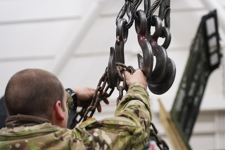 A soldier assigned to the 109th Transportation Company, 17th Combat Sustainment Support Battalion, U.S. Army Alaska, attaches chains to a hoist to move a damaged engine from an M984A2 Heavy Expanded Mobility Tactical Truck wrecker onto jack stands in his unit's motor pool on Joint Base Elmendorf-Richardson, Alaska, Dec. 13, 2019. The M984A2 is an eight-wheel drive, diesel-powered, variant of the HEMTT used in vehicle recovery operations.