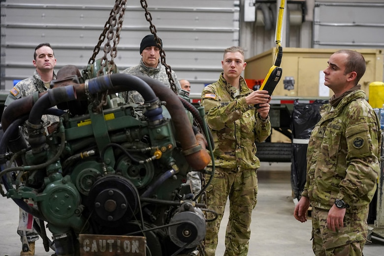 Army Spc. Bradley McAfee, a native of Reading, Penn., center, assigned to the 109th Transportation Company, 17th Combat Sustainment Support Battalion, U.S. Army Alaska, controls a hoist while moving a damaged engine from an M984A2 Heavy Expanded Mobility Tactical Truck wrecker his unit's motor pool on Joint Base Elmendorf-Richardson, Alaska, Dec. 13, 2019. The M984A2 is an eight-wheel drive, diesel-powered, variant of the HEMTT used in vehicle recovery operations.